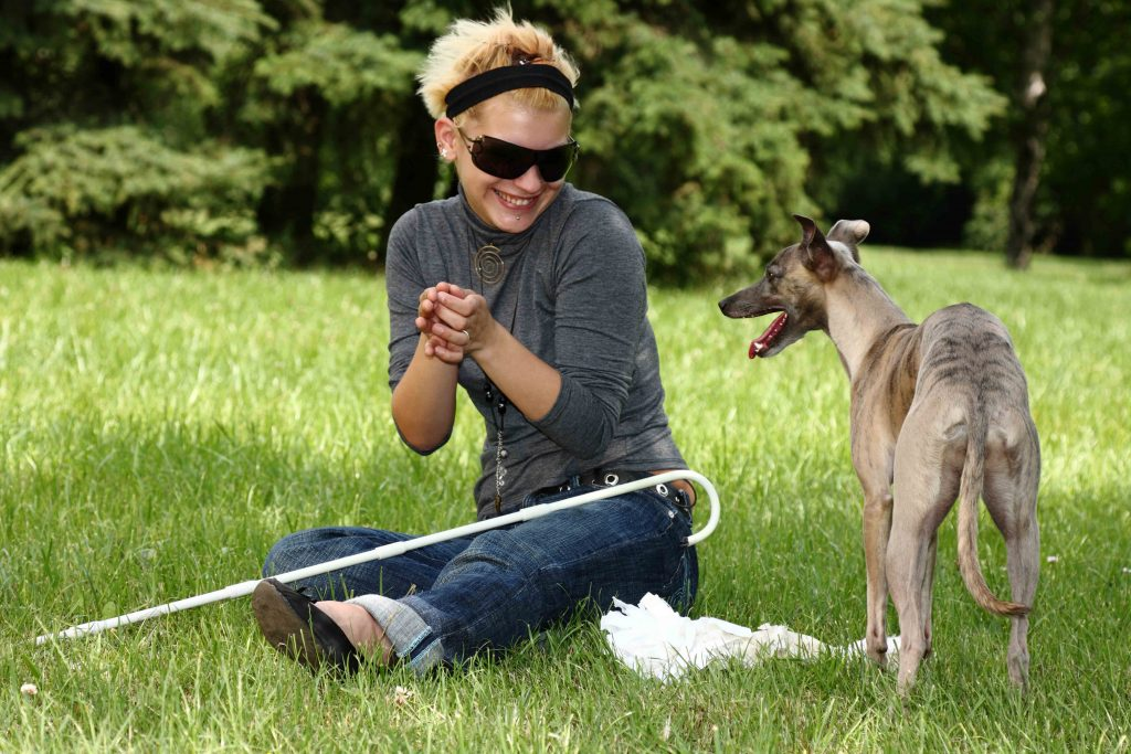 Blind lady in the park with her dog