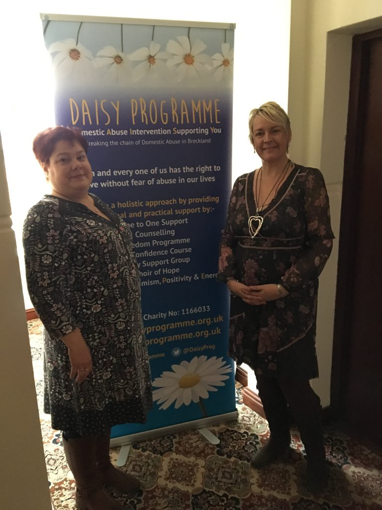workers from the daisy programme stand with their banner